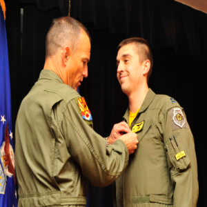 Brig. Gen. Scott Pleus, 56th Fighter Wing commander, pins the Air Force Combat Action Medal onto Capt. Aaron Cavazos, 61st Fighter Squadron weapons officer, Jan. 16 in Club Five Six at Luke Air Force Base. Cavazos was awarded the Air Force Combat Action Medal and the Distinguished Flying Cross with Valor for his heroism while serving in Operation Enduring Freedom Oct. 28, 2008. Cavazos efforts saved the lives of six Marines that day. (U.S. Air Force photo/Senior Airman Grace Lee)